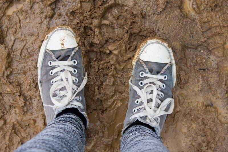 Smutsiga skor på en lerig yttersida arkivfoto