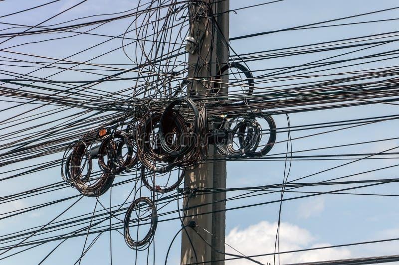 Smutsiga trådar som fästas till den elektriska masten royaltyfria foton