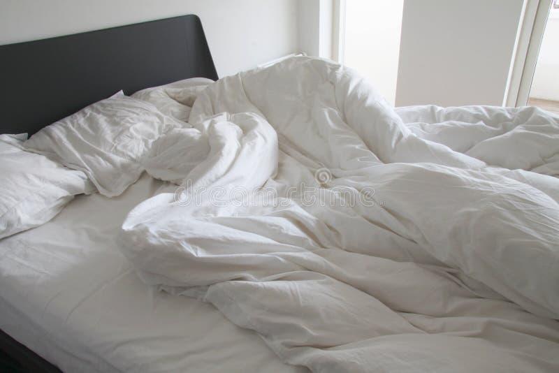 Smutsiga vita bädda ned ark och kuddar med skrynklor på säng i ett vitt sovrum - materiel arkivbilder