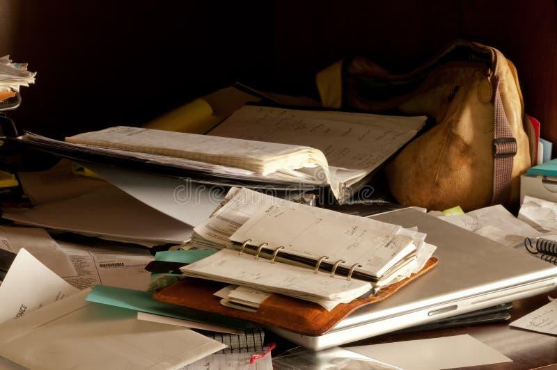 Smutsigt desorganiserat skrivbord royaltyfria bilder