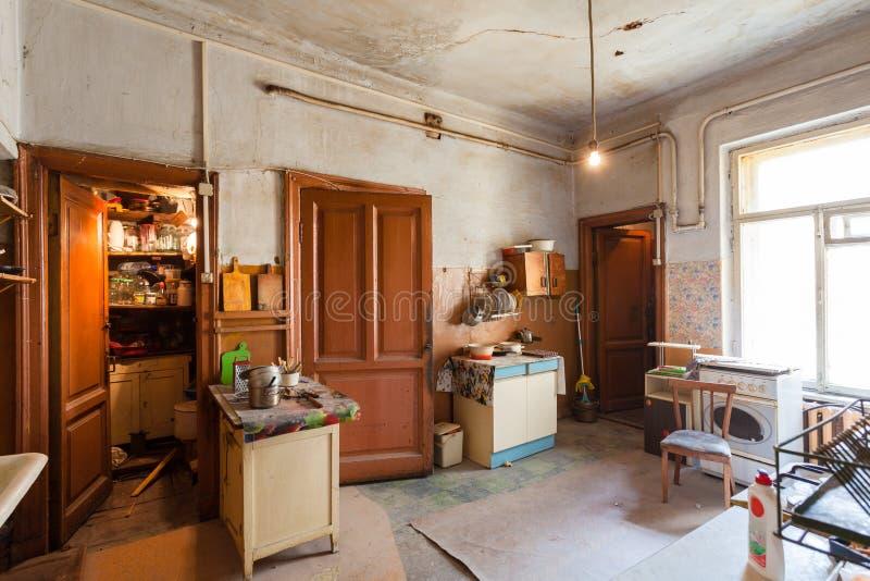 Smutsigt kök med möblemang- och gasugnar är i lägenheten för tillfälliga bosatta existensflyktingar som tvingades till mig fotografering för bildbyråer