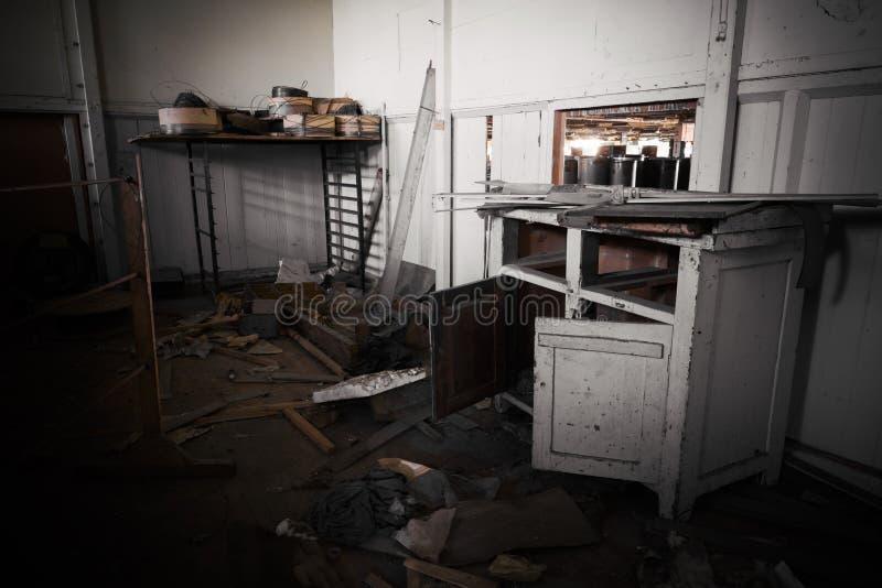 Smutsigt kontorsmöblemang i en övergiven fabrik royaltyfri foto