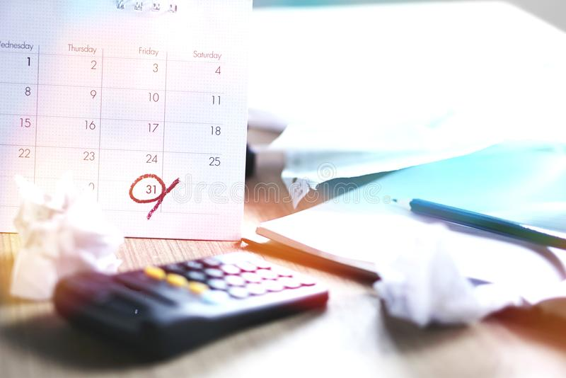 Smutsigt kontorsskrivbord under skattsäsong med stopptid på en kalender royaltyfri bild