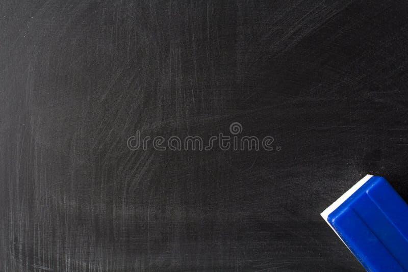 Smutsigt svart tavla och radergummi arkivbild