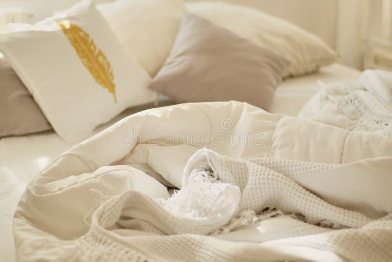 smutsigt underlag Vit kudde med filten på ogjord säng Begrepp av att koppla av efter morgon Med belysningfönstret Top beskådar de arkivbild