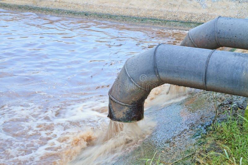 Smutsigt vatten flödar från ett rör. arkivbild