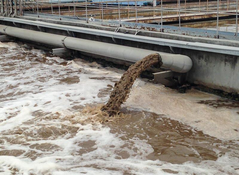 Smutsigt vatten flödar från ett rör royaltyfri foto