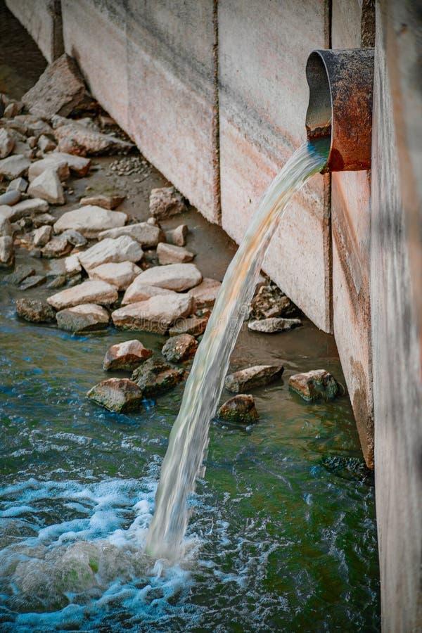 Smutsigt vatten som urladdar in i floden royaltyfri foto