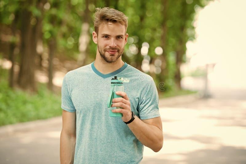 Smutt av friskhet efter stor genomk?rare Man med den idrotts- utseendeh?llflaskan med vatten Idrottsman nendrinkvatten after royaltyfria foton