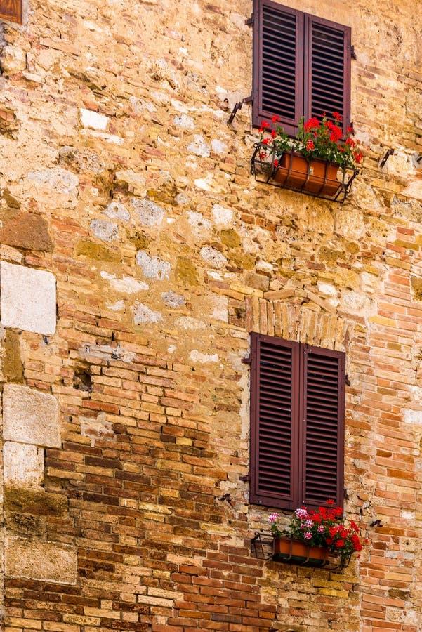 Smyckade fönster i de medeltida gatorna av San Gimignano royaltyfri foto