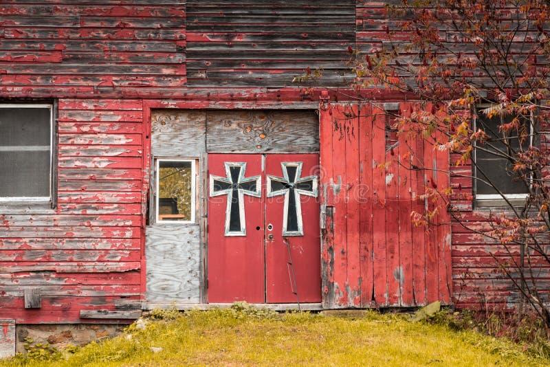 Smyckas dubbla dörrar för röd ladugård i stora gotisk-stil kors som omges av nedgånglövverk royaltyfri bild