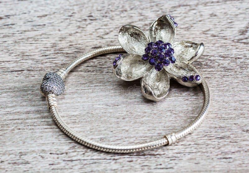 Smycken, armbandet och broschen för kvinna` s blommar royaltyfri foto