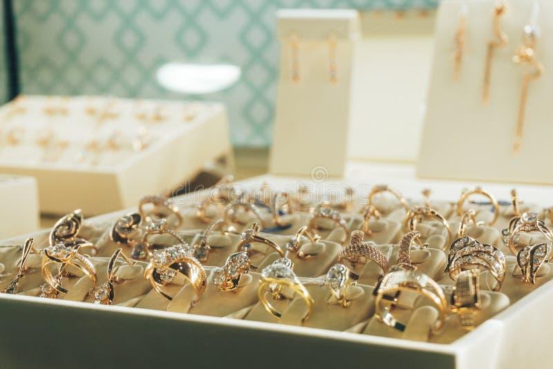 Smycken i shoppafönstret, guld- cirklar med diamanter, kopieringsutrymme arkivbild