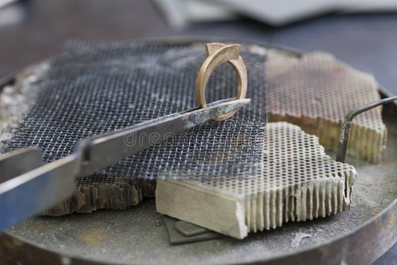 Smyckendanandehand som tillverkar en metallcirkel royaltyfri fotografi