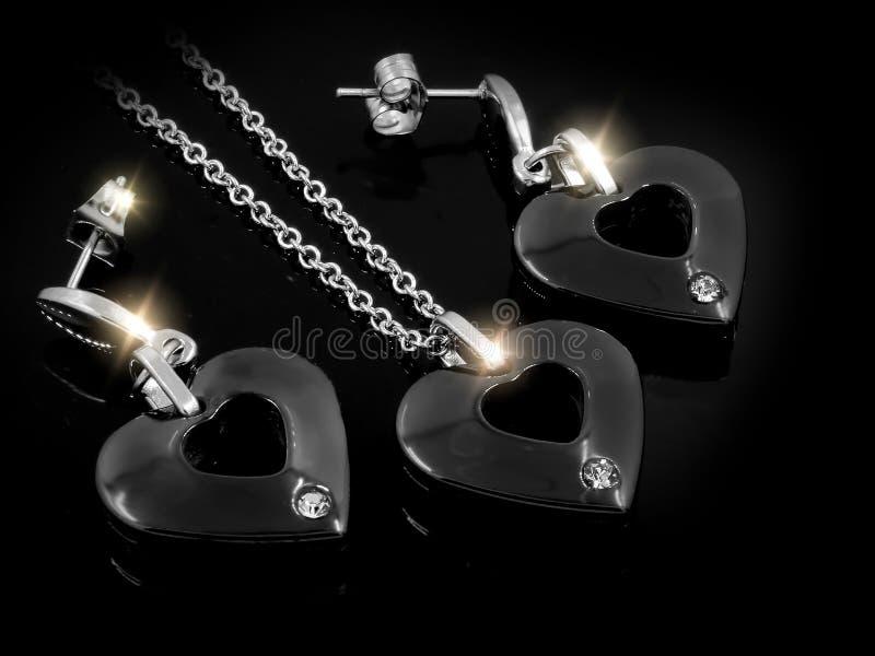 Smyckenuppsättning - halsbandet och örhängen - rostfritt stål och Zircons arkivbilder