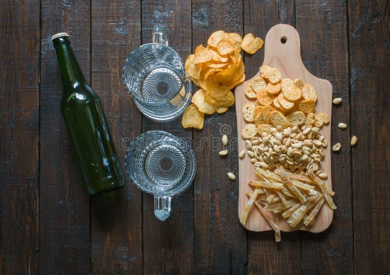 Snäcke zum Bier, auf einem hölzernen Brett und zwei leeren Bechern, auf einem Holztisch Chips, Erdnüsse, Stücke Fische, Cracker,  stockfotos