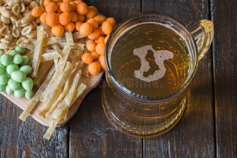 Snäcke zum Bier und zum Becher hellem Bier, auf einem Holztisch, in einer Bar Erdnüsse, Erdnüsse in einem Oberteil, Stücke Fische lizenzfreies stockfoto
