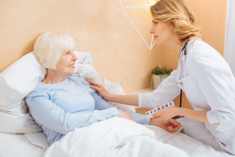 Snäll ansvarig doktor som övertalar hennes höga patient för att bli i säng royaltyfria foton