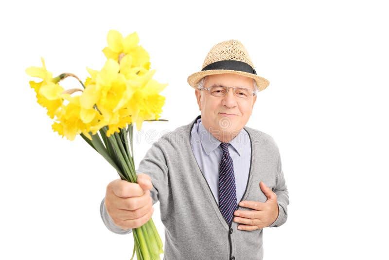 Snäll hög gentleman som ger blommor till någon royaltyfri bild