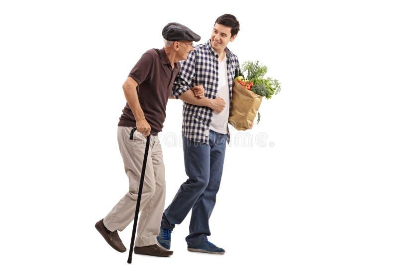 Snäll man som hjälper en pensionär med livsmedel royaltyfri foto