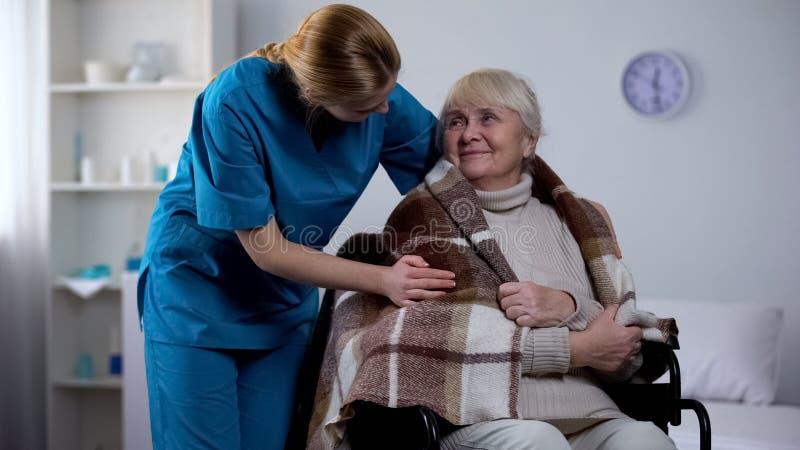 Snäll sjuksköterskabeläggning med den handikappade gamla kvinnan för filt, sjukhusomsorg, service fotografering för bildbyråer