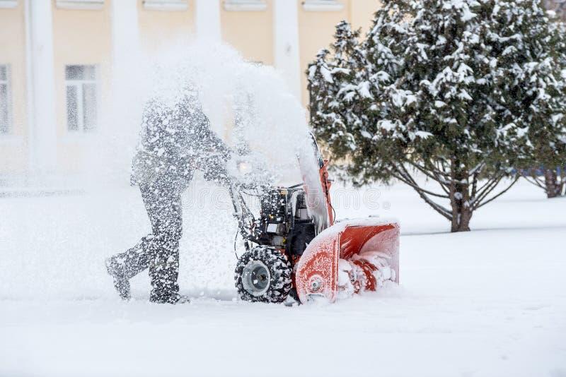 Snö-borttagning arbete med en snöblåsare man som tar bort snow tung nederbörd- och snöhög royaltyfri bild