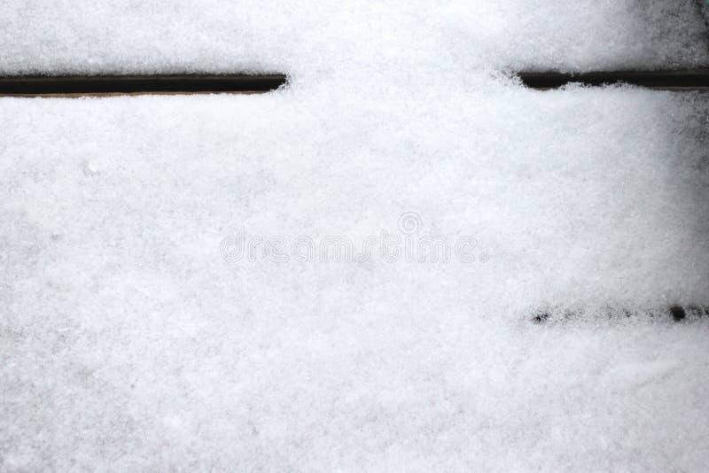 Snö flagar över trägolvet, vinterbakgrund arkivbild