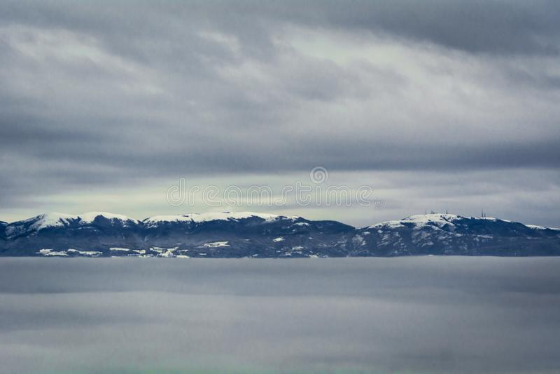 Snö-korkade berg i den iskalla klara vinterhimmelgrodden från ett hav av moln royaltyfri foto