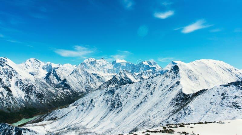 Snö-korkade berg mot den blåa himlen i den Altai republiken arkivbilder