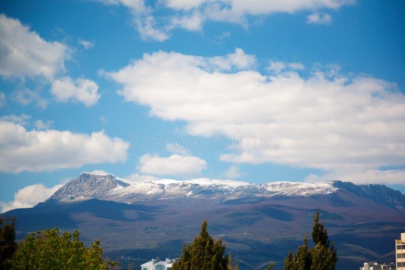 Snö-korkade bergmaxima och vitmoln fotografering för bildbyråer