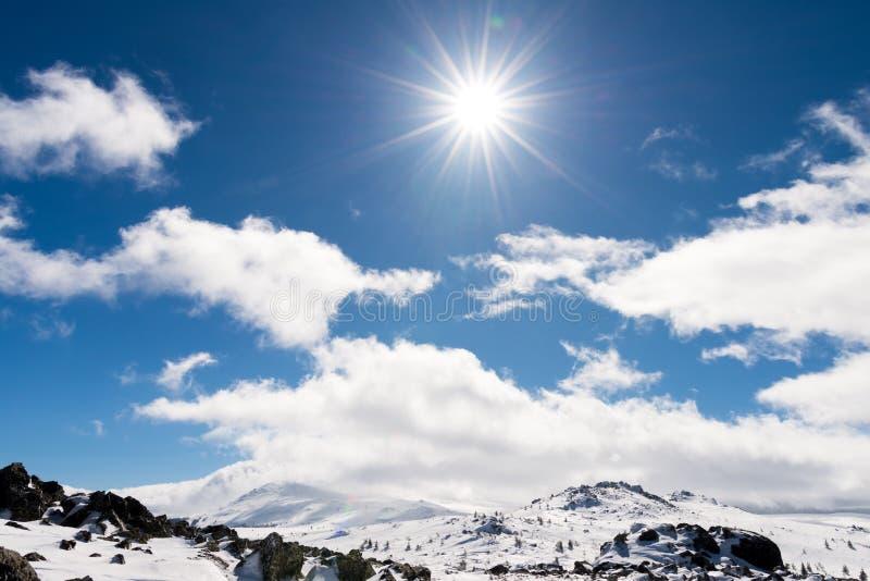 Snö-korkat berglandskap och solstrålar i himlen arkivbilder