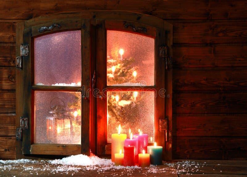 Snö och stearinljus på fönstret förser med rutor arkivbild