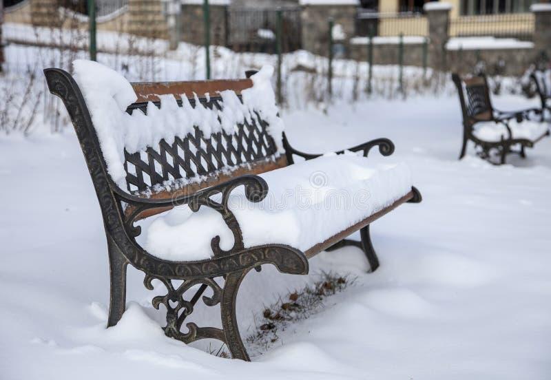 Snö på bänk parkerar in av vinter fotografering för bildbyråer