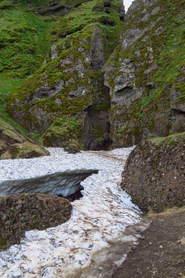Snö på ingången av den smala Raudfeldsgja kanjonen, Budir, Snæfellsnes, Island royaltyfri fotografi
