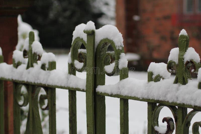 Snö på smidesjärnportar arkivbilder