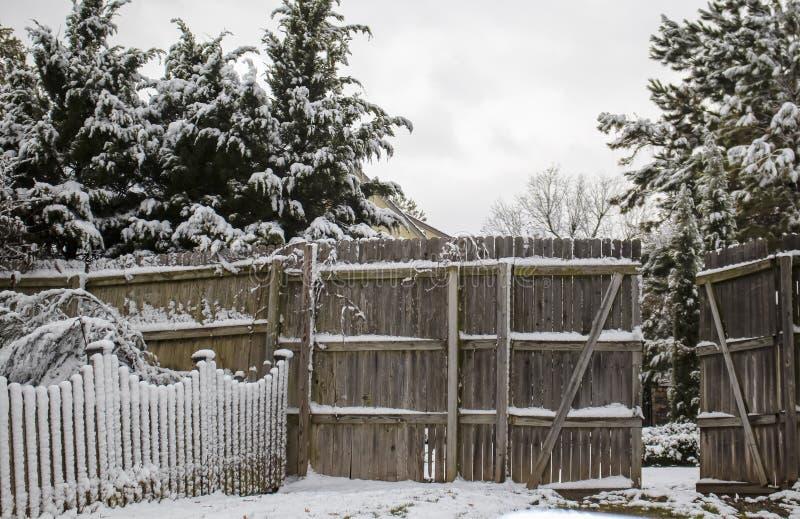 Snö på staketet för avskildhet för posteringstaket det skärande med den öppna porten och vintergröna träd bakom royaltyfria bilder