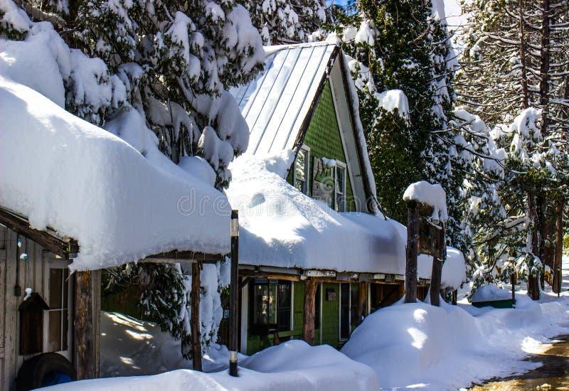 Snö täckt byggnad med det nådde en höjdpunkt taket arkivbild
