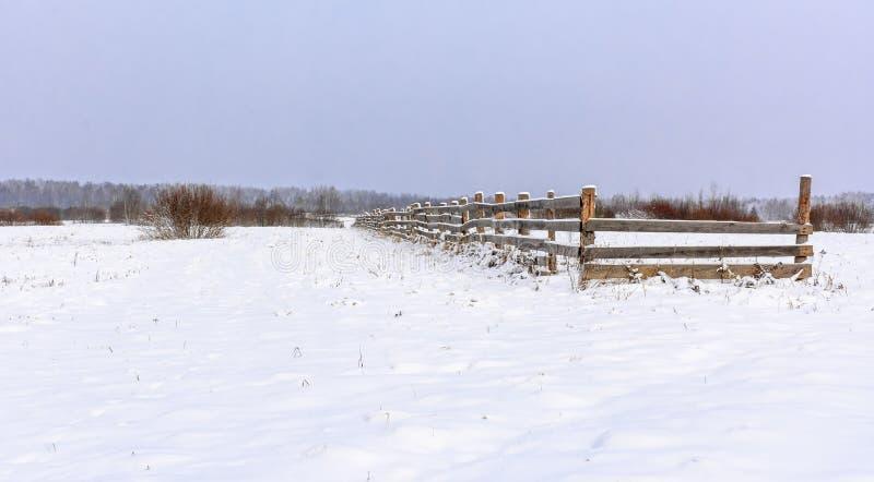 Snö-täckt fält i bygden Ett trästaket av jordbruksmark royaltyfri fotografi