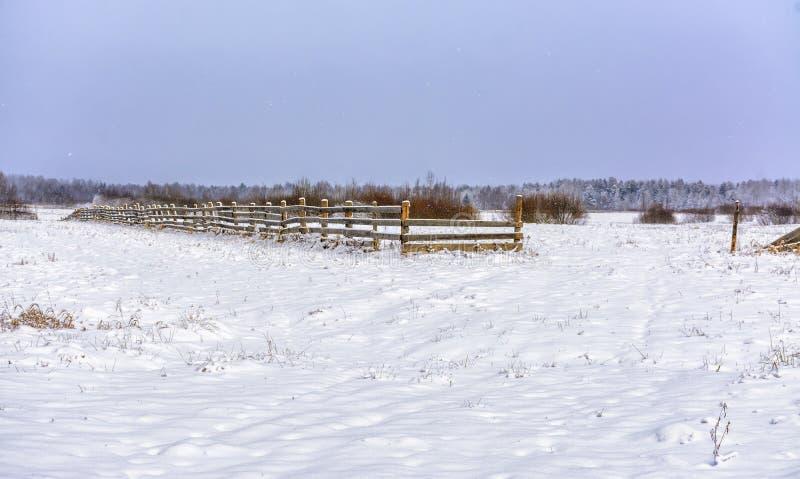 Snö-täckt fält i bygden Ett trästaket av jordbruksmark arkivfoto