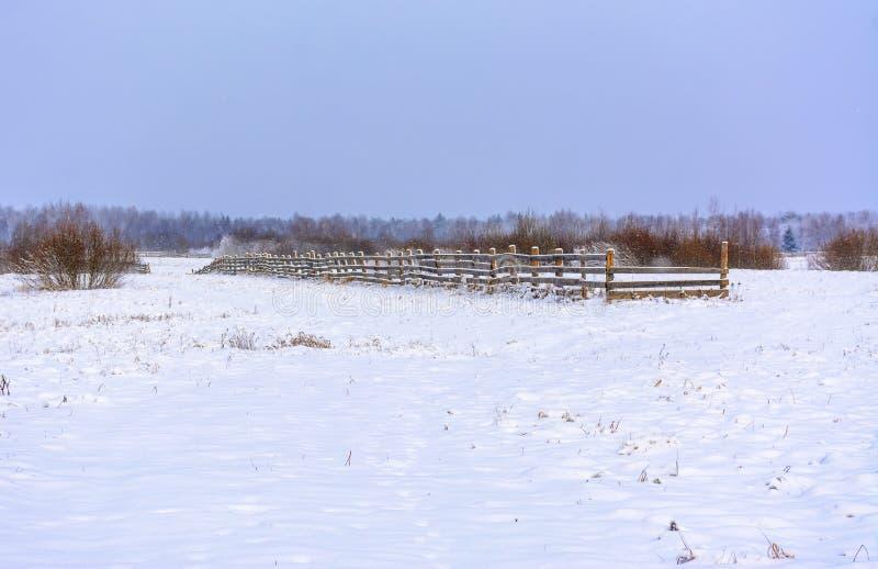 Snö-täckt fält i bygden Ett trästaket av jordbruksmark fotografering för bildbyråer