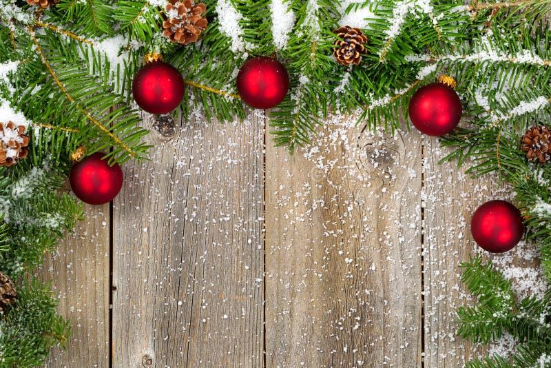 Snö täckt gran förgrena sig med röda prydnader och kottar på lantligt royaltyfri bild