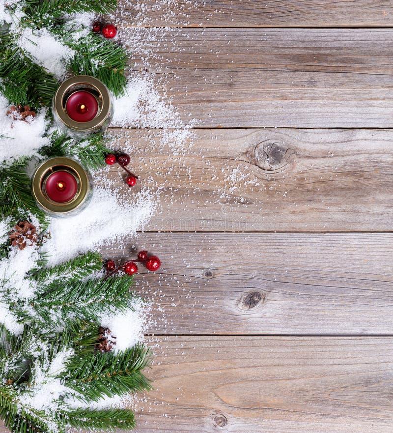 Snö täckt julgran förgrena sig och stearinljus på lantligt trä fotografering för bildbyråer