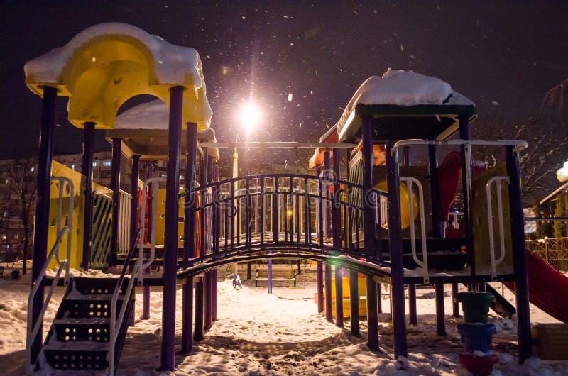 Snö-täckt lekplats på natten i staden i vinter royaltyfri bild