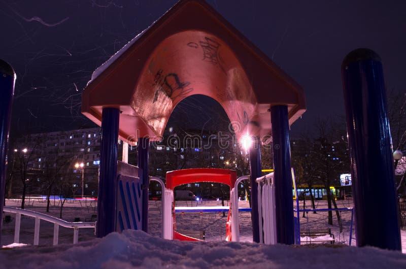 Snö-täckt lekplats på natten i staden i vinter royaltyfri foto