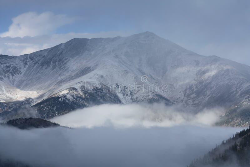 Snö-täckte berg i molnen arkivfoto