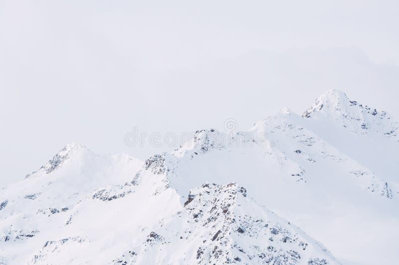 Snö-täckte bergmaxima mot den molniga himlen arkivfoton