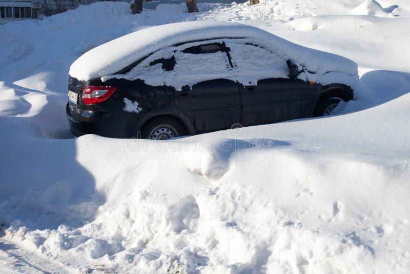 Snö-täckte bilar på parkeringsplatsen, en snöstorm i Ryssland Hjälpmedel för snöborttagning royaltyfria foton