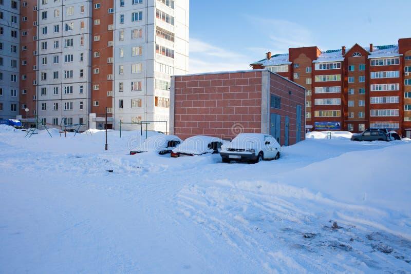 Snö-täckte bilar på parkeringsplatsen, en snöstorm i Ryssland Hjälpmedel för snöborttagning royaltyfri bild