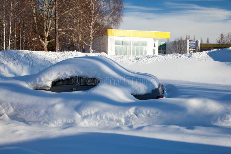 Snö-täckte bilar på parkeringsplatsen, en snöstorm i Ryssland Hjälpmedel för snöborttagning royaltyfri foto