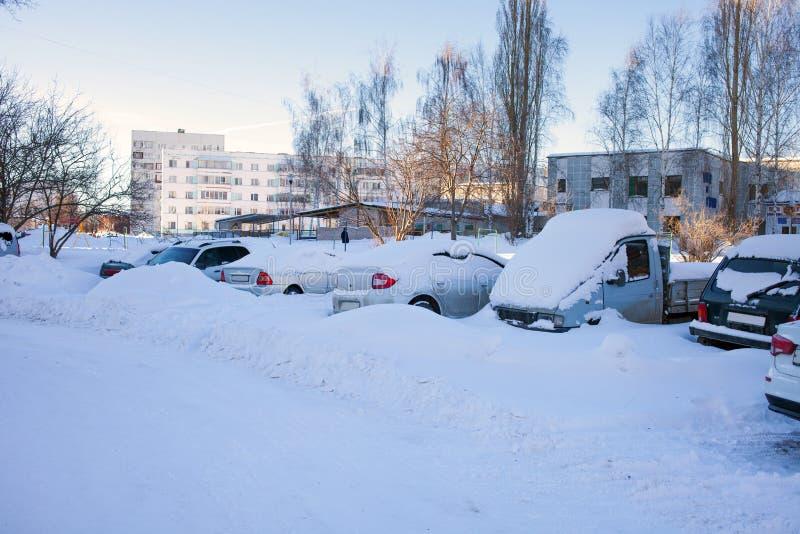 Snö-täckte bilar på parkeringsplatsen, en snöstorm i Ryssland Hjälpmedel för snöborttagning arkivfoto